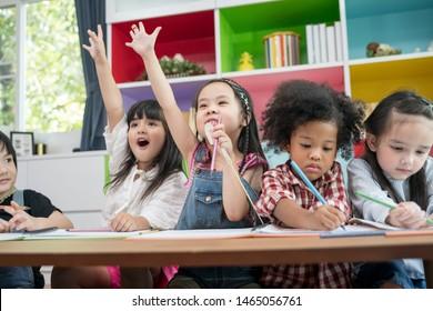 Group of little preschool kids drawing paper with color pencils . portrait of children friends education concept.
