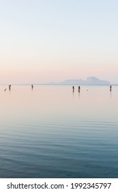 A group of local fishermen serching for seashells in the shoreline at sunrise after the monsoon season. Hat Chao Mai Beach, Trang, Thailand.
