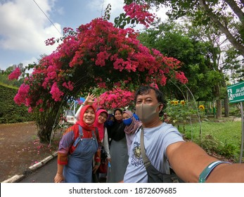 A group of local tourists poses at the mass of the new normal covid-19 in the Coban Rondo waterfall area, Batu City, East Java, Indonesia on August 12, 2020