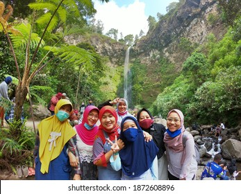 A group of local tourists poses at the new normal covid-19 mass at Coban Rondo waterfall, Batu City, East Java, Indonesia on August 12, 2020
