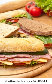 group of long baguette and toasted sandwiches with lettuce, vegetables, salami, ham and cheese on a cutting board and ingredients