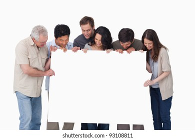 Group looking at blank sign in their hand against a white background
