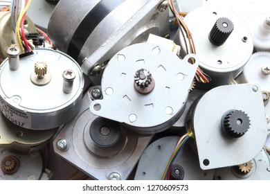 A group of low power brushless stepper motors with gears on their shaft, found in small electronic devices like printers, with cables, on white