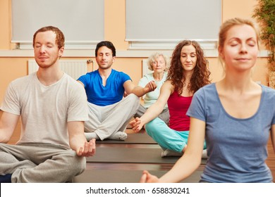 Group making breathing exercise during meditation in yoga class