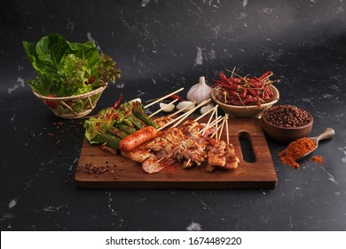 Group of Mala grilled barbecue (BBQ) with Sichuan pepper, Hot and spicy and delicious street food on wood board and ingredients ( Chilli,Sichuan pepper ,Garlic) food on black background.