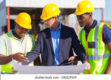 group of male architect and construction workers on construction site
