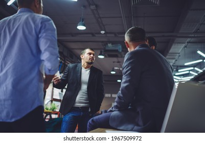 Group of male colleagues discussing business strategy during workshop brainstorming in office interior, smart casual men talking about trade exchange and financial experience communicate in firm