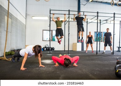 Group of male and female athletes exercising in gym