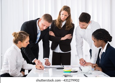 Group Of Male And Female Businesspeople Analyzing Graph In Office