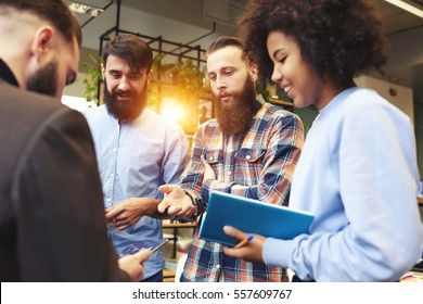 Group of male and female IT developers discussing ideas about new successful project during informal meeting with team leader using digital device and wireless connection to fast 4G internet in office