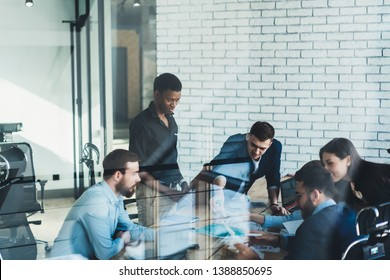 Group of male and female entrepreneurs discussing management project during working together in modern office, confident business people analyzing accounting trade and experience about proud ceo