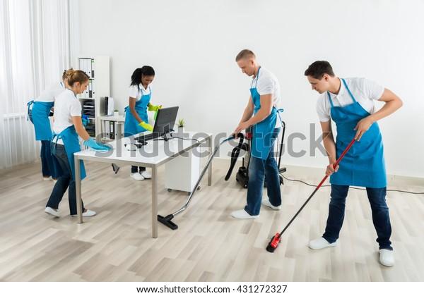 Gruppe männlicher und weiblicher Janitoren in einheitlicher Reinigung des Amtes