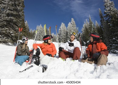Group of male and female skiers sitting in the snow relaxing talking and smiling. Horizontal shot.