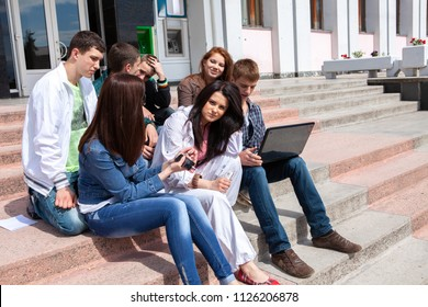 Group of male and female students against the background an academic building