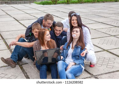 Group of male and female students sitting with a laptop on street