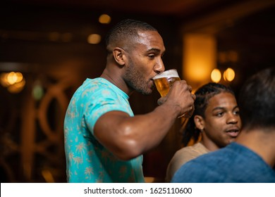 A group of male friends drinking together in a bar. The main focus is on a man drinking a pint of beer.