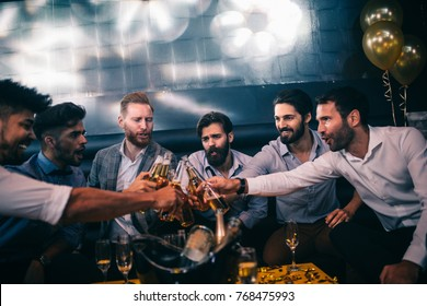 Group of male friends having celebrating in the club