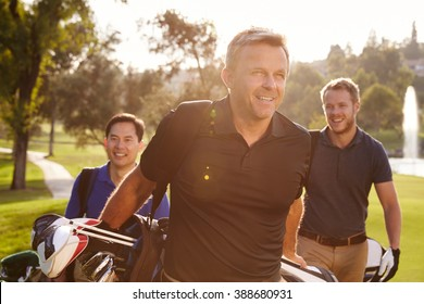 Group Of Male Golfers Walking Along Fairway Carrying Bags