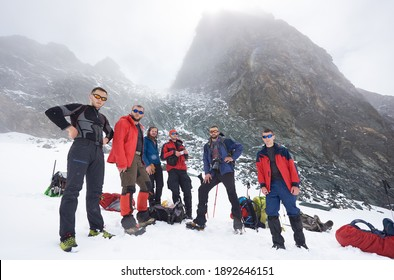Group of male hikers in sunglasses standing on snow covered filed at the bottom of mountain looking at camera while taking break during hike. Concept of travelling, hiking and mountaineering.
