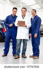 Group of male mechanics smiling at a car repair shop