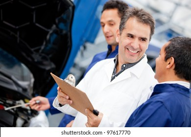 Group of male mechanics working at a car garage