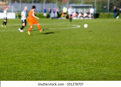 Group of male soccer players playing amateur soccer match on sunny summer day on simple sports venue in Denmark.