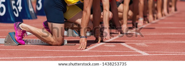 Group of male track athletes on starting blocks.Hands on the starting line.Athletes at the sprint start line in track and field