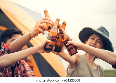 Group of man and woman enjoy camping picnic and barbecue at lake with tents in background. Young mixed race Asian woman and man. Young people's hands toasting and cheering beer. Vintage filtered image