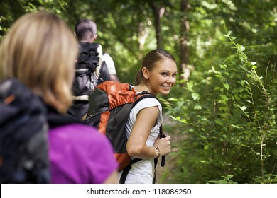 group of man and women during hiking excursion in woods, with woman looking at camera over shoulders and smiling. Waist up