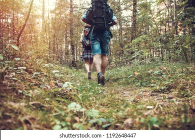 group of man and women during hiking excursion in woods, walking while enjoying their journey. Low section view