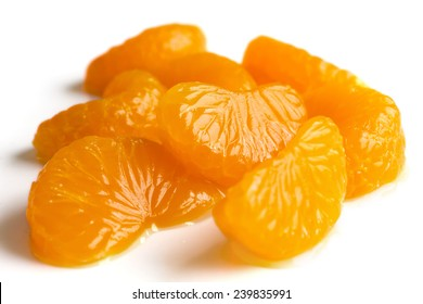 Group of mandarin segments in light syrup on white.