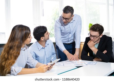 Group of marketing experts analyzing paper reports. Four young colleagues discussing and studying business diagrams at meeting table. Business team and expertise concept