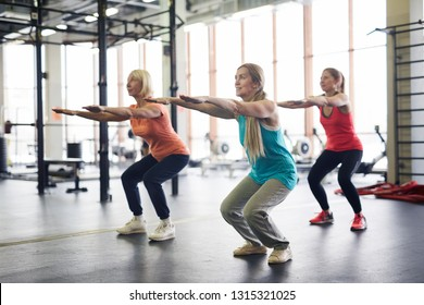 Group of mature active females squatting and stretching arms forwards during workout in fitness center