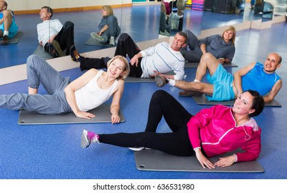 Group of mature adults doing pilates routine in a sport club