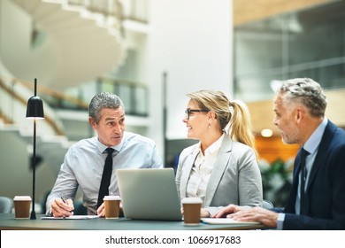 Group of mature businesspeople sitting at a table in the lobby of a modern office discussing work and using a laptop