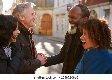 Group Of Mature Friends Meeting Outdoors In City