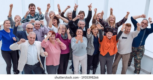 group of mature friends raised their hands up and celebrate succ