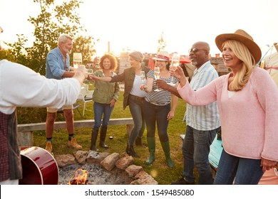Group Of Mature Friends Sitting Around Fire And Making A Toast At Outdoor Campsite Bar