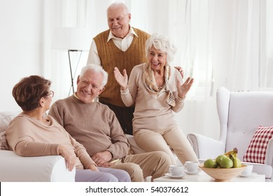Group of mature friends talking and smiling in light room