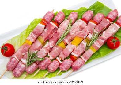 group of meat skewers on dish on white background