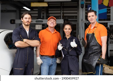 Group of mechanic worker success after worker, service and maintenance in the garage. Confidence male and female technician worker standing together in the automotive spare parts storage warehouse
