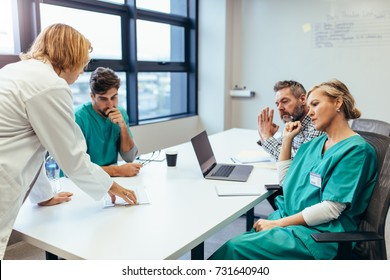 Group of medical professionals brainstorming in a meeting. Team of healthcare workers discussing in boardroom, with female doctor presenting her plan.