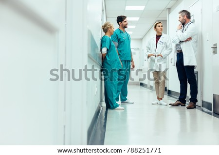 Group of medical staff discussing in clinic hallway. Healthcare professionals having discussion in hospital corridor.