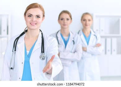 Group of medicine doctors offering helping hand  for shaking hand or saving life. Partnership and trust concept in health care or medical cure
