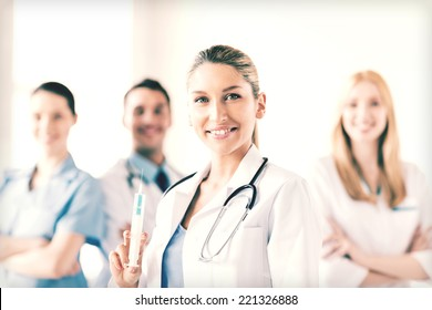 group of medics with female doctor holding syringe with injection