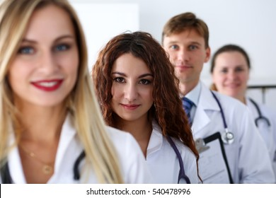 Group of medics proudly posing in row and looking in camera smiling. High level service, best treatment, 911, professional, healthy lifestyle, therapeutist consultation, physical, emergency concept