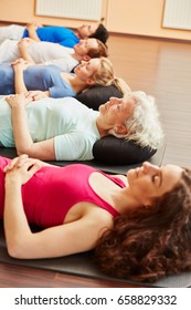 Group meditating for relaxation after yoga class