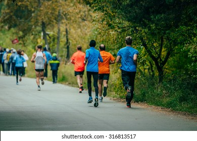 group of men athletes runners running in autumn Park during marathon. rear view
