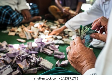 A group of men counting charity money at a mosque.