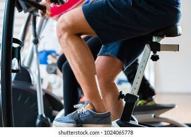 Group of men doing workout on exercise bike at gym